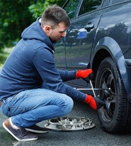 man changing tire because of a flat