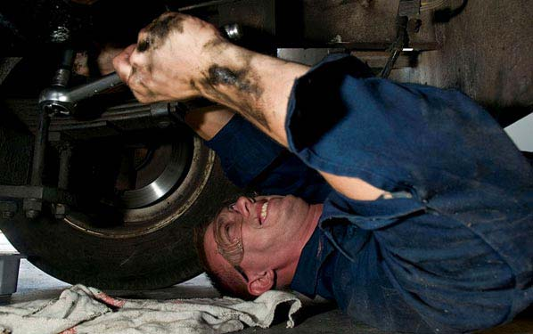 A mechanic performs a routine oil change